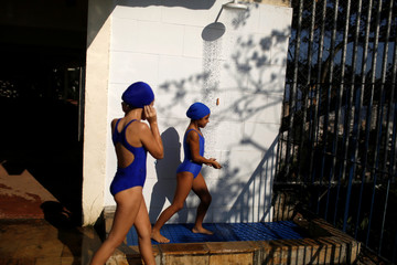 Girls take a bath before entering a swimming pool for their swimming class at the 'Crianca Esperanca' (Child Hope) social project in Cantagalo slum in Rio de Janeiro