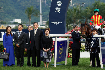 "British jockey Ryan Moore riding ""Maurice"" from Japan poses for photo with owner Katsumi Yoshida and his wife Kazumi after winning the 2,000m Longines Hong Kong Cup Group One race at Sha Tin Racecourse in Hong Kong, China"