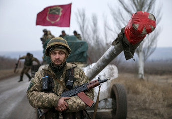 A member of the Ukrainian armed forces stands guard as a convoy of the Ukrainian armed forces including armoured personnel carriers, military vehicles and cannons prepare to move as they pull back from Debaltseve region, in Paraskoviyvka
