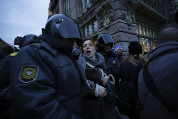 Police detain a woman protesting against the outcome of a trial against protesters in Moscow, at a rally in central Saint-Petersburg