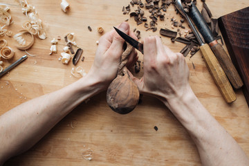 Wood carving, the master's hands work with a wooden surface, a professional does wood crafts