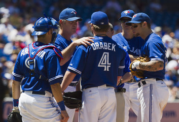 Blue Jays manger Farrell talks to pitcher Drabek as Arencibia, Johnson, and Lawrie look on before Drabek left the game on a possible injury against the Washington Nationalsduring their MLB baseball game in Toronto