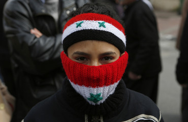 A boy wearing a headband and scarf in the colours of the Syrian flag takes part in a rally in Majdal Shams on the Golan Heights