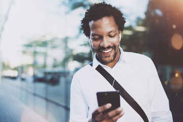 Happy young African American man in headphone walking at sunny city and making video conversation with friends on his electronic smart phone.Blurred background.