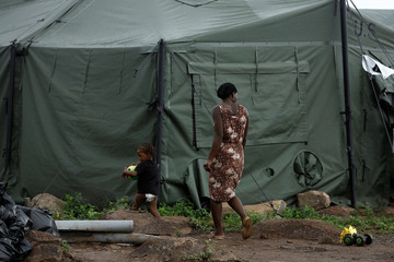 A Haitian migrant and her son walk at a makeshift camp at the border between Costa Rica and Nicaragua, in La Cruz