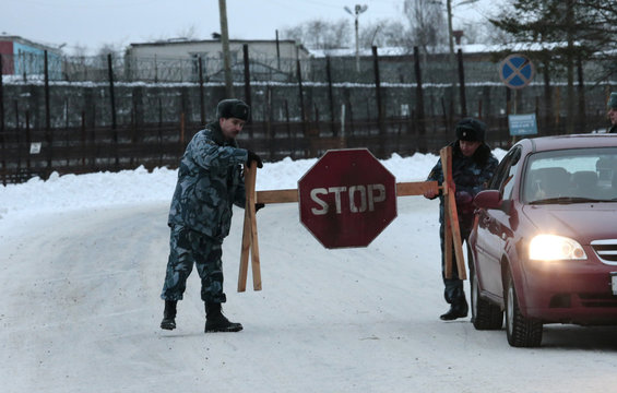 Police officers install a stop sign on a road leading to the Penal Colony No. 7 where Mikhail Khodorkovsky was held at the village of Segezha