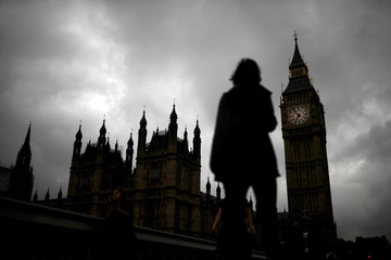 A woman walks past the Houses of Parliament and the Big Ben clock tower, on the day of the EU referendum, in central London