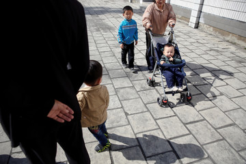 A woman pushes a baby in stroller outside a subway station in central Pyongyang,