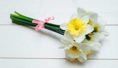 Bright yellow daffodils on white wooden table, selective focus. Yellow and white narcissus. Greeting card