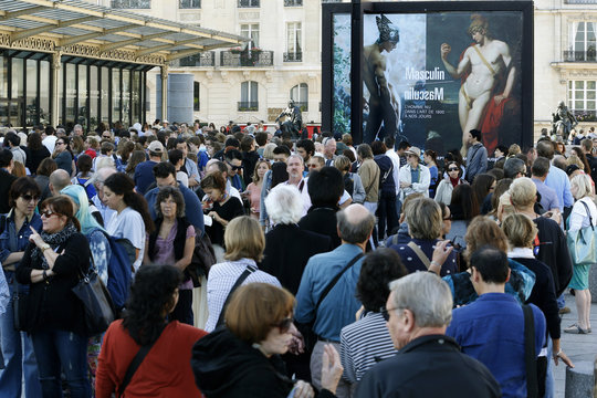 People stand in line outside the Musee d'Orsay on the first day of the exhibition 'Masculine / Masculine. The Nude Man in Art from 1800 to the Present Day' in Paris
