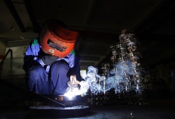 A labourer welds at a valve factory in Wenzhou