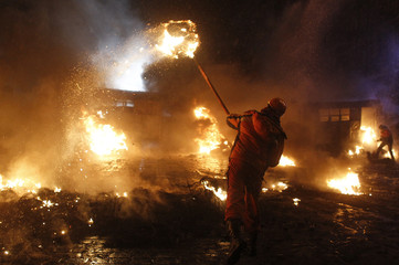 A pro-European protester throws a burning tyre during clashes with riot police in Kiev