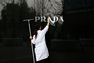 A woman cleans the brand logo at a Prada fashion boutique in Beijing