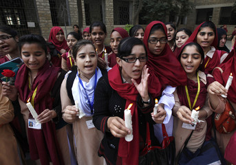 Students gather to pray and pay tribute to the victims of the Pakistan Taliban attack on the Army Public School in Peshawar, at a school in Karachi