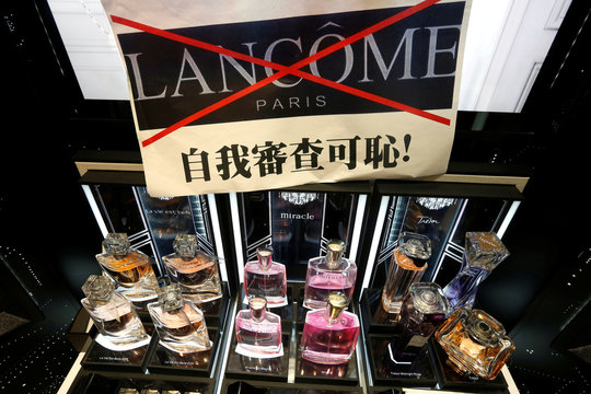 A placard by protesters is displayed on top of products of the luxury skincare brand Lancome, inside a shopping mall in Hong Kong
