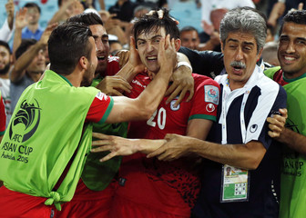 Iran's Sardar Azmoun is mobbed by team mates after scoring a goal against Qatar during their Asian Cup Group C soccer match at the Stadium Australia in Sydney