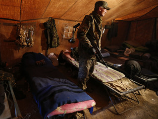 A Ukrainian serviceman stands inside his tent at the military camp in the village of Luhanske