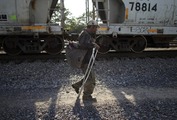 A migrant from El Salvador walks next to the train tracks with the help of a crutch after he injured himself while riding the train through Mexico, on the outskirts of Monterrey