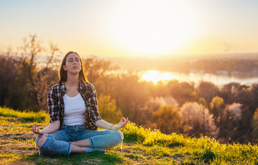 Woman relaxing on the sunset light in the mountain doing yoga lotus position