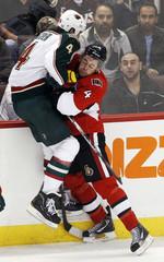 Ottawa Senators' Phillips hits Minnesota Wilds' Stoner during their NHL hockey game in Ottawa