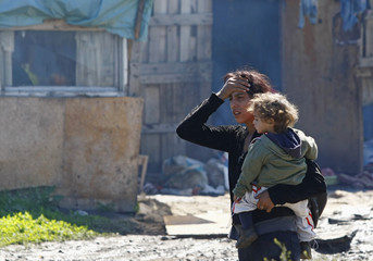 A Roma woman holds her child while she waits to be evacuated from a slum in Belgrade