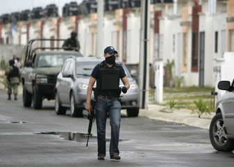 A federal police officer walks on a street during a joint operation with the army in a neighborhood in Cancun