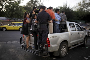 People ride in the back of of a goverment pick up truck during the fourth day of a suspension of public transport services in San Salvador