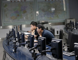 Staff members of the Beijing Municipal Environmental Protection Monitoring Center work in a monitoring room of the air quality forecast and warning center in Beijing
