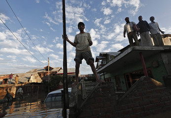 A Kashmiri family stand on roof of their flooded house as they wait to be rescued in Srinagar