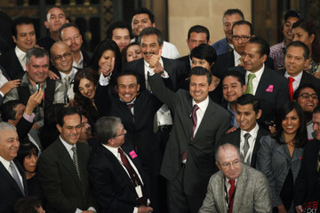 Mexican President Nieto and Mexican boxer Marquez raise their hands while they pose with journalists during a recognition ceremony at National Palace in Mexico City
