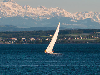 Spoed Foto op Canvas Zeilen Sailing boat on a lake with Alps in background
