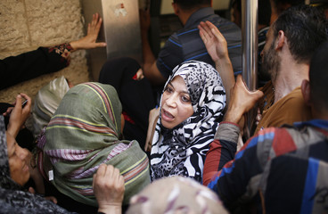 Palestinian employees paid by the Palestinian Authority wait to withdraw cash from an ATM machine outside a bank, in Gaza City