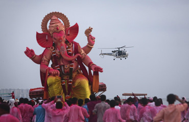 An Indian Coast Guard helicopter flies past devotees carrying an idol of Hindu elephant god Ganesh for immersion into the Arabian Sea during the Ganesh Chaturthi festival in Mumbai