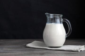 Jug of fresh milk om wooden table against black background. Copy space.