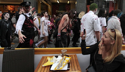 A woman takes a picture of enthusiasts dressed as zombies walking past a restaurant during the annual Zombie Walk festival in Prague