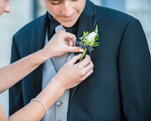 Handsome Mexican teen receiving help with boutonniere on formal black suit.