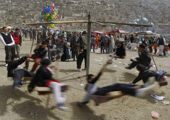Afghan children play on a swing during a gathering to celebrate the Afghan New Year (Nawroz) in Kabul