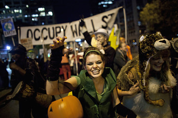 """A woman dressed up in a costume walks in front of an """"Occupy Wall Street"""" banner during the 39th Annual Halloween Parade in New York"""
