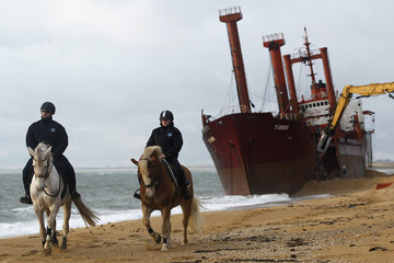 Security officers patrol the beach as a crane dismantles the Maltese-registered cargo ship the TK Bremen on Kerminihy beach at Erdeven