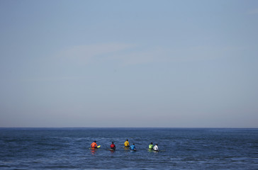 A group of contestants wait for a wave during the Mavericks Invitational surf competition in Half Moon Bay