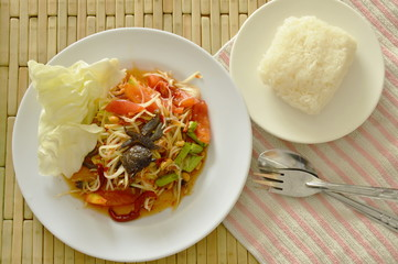 Somtum Thai spicy green papaya and black pickled crab salad eat with sticky rice