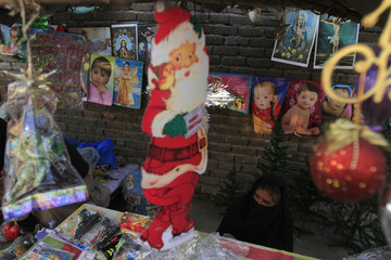 A picture of Santa Claus is displayed at a stall as a woman waits for customers at a Christian slum in Islamabad