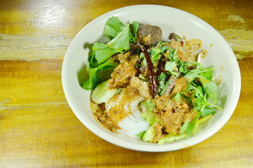 rice noodles dressing spicy minced pork and bone red cotton tree sauce with vegetable on bowl