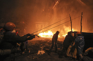 Pro-European integration protesters use a big slingshot during clashes with riot police in Kiev