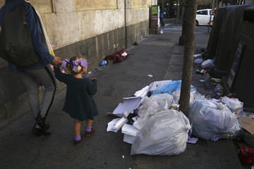 A girl walks past garbage on the second day of an indefinite strike by street cleaners in Madrid