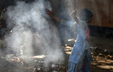 A girl plays amidst the smoke from the burning garbage outside a public toilet in Mumbai