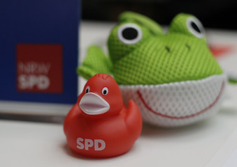 A red plastic duck with the logo of the SPD is seen next to a green plastic frog during a NRW SPD party congress in Duesseldorf