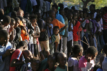 Thousands of Haitians wait in the early morning light for food and water in Port-au-Prince