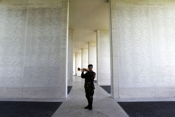 A soldier plays a trumpet beside a wall bearing names of missing soldiers as preparations for Veterans Day are made in the U.S. cemetery in Fort Bonifacio