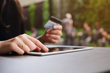 close up woman hand touch screen on tablet pad and holding credit card for shop online